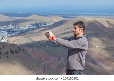 Young man photographing a beautiful mountain view