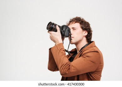 Young man photographing on professional camera isolated on a white background