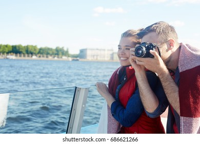 Young man photographing river sights during cruise with his girlfriend or wife