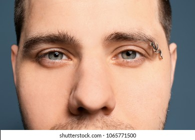 Young Man With Pierced Eyebrow On Color Background Closeup