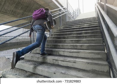 Young man with pink backpack running up the flight of stairs in an urban setting