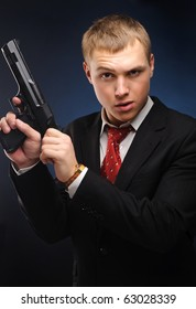 Young man with pistol over dark background