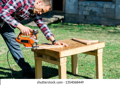 Young man in plaid shirt doing some carpentry work in his backyard using electric jigsaw. Do it yourself.