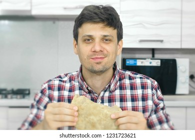 Young man in a plaid shirt eats a big cheburek with an appetite.