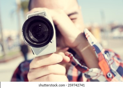 a young man with a plaid shirt filming with a Super 8 camera outdoors