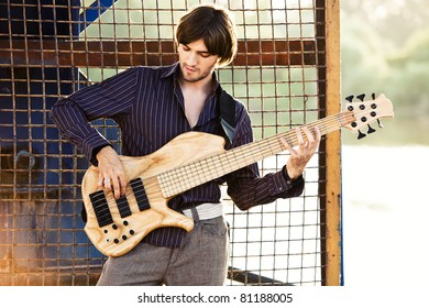 young man play bass guitar at industrial area by the river at sunset