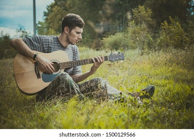 Young man play on acoustic guitar sitting on the grass walley. Maybe blues man or country musician