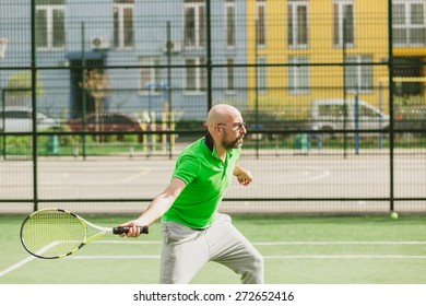 young man play tennis outdoor on tennis field at early morning
