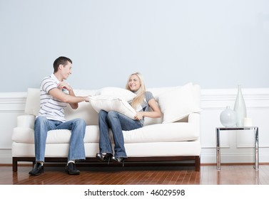 Young man playfully hits a young woman with a pillow on the sofa. Horizontal shot.