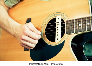 Young man playing the acoustic guitar using plectrum. Focus on the hand.