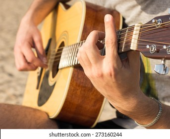 young man playing an acoustic guitar on the beach