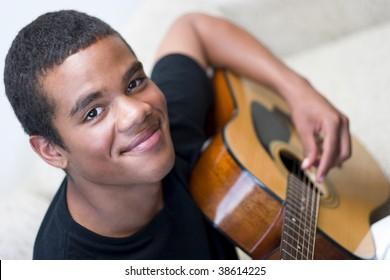 Young man playing an acoustic guitar, closeup.