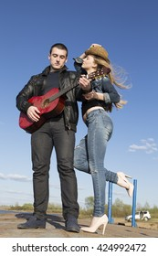 Young man playing acoustic guitar and smiling woman holding her hat