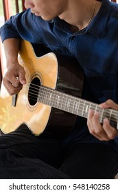 A young man playing acoustic guitar happy and relaxed in the daytime focal point on the details.