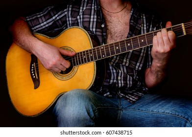 Young man playing acoustic guitar - isolated on black background