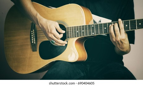 a young man playing acoustic guitar in studio