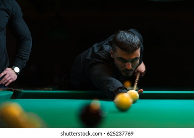 Young man playing billiard in dark club.