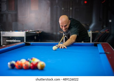 Young man playing billiard in a pool hall