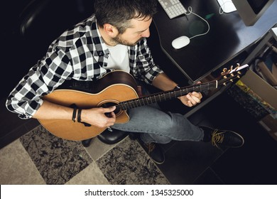 Young man playing classical guitar in studio.Concept of musician guitarist