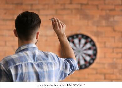 Young man playing darts indoors