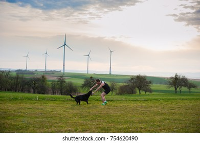 young man playing with a dog on the field