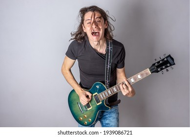 A young man is playing an electric guitar singing and waving his long hair. Emotional performance of rock and roll