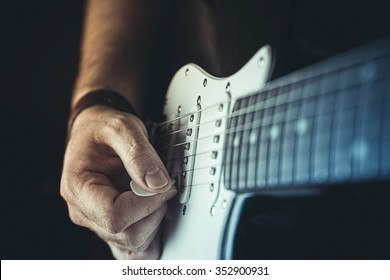 Young man playing electric guitar. Music, instrument education and learning concept