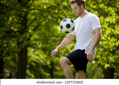 Young man playing football in park keeping ball in the air