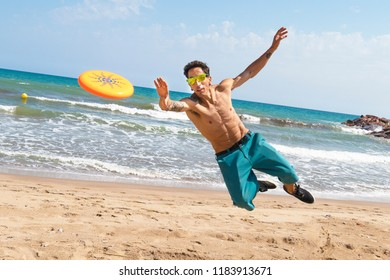 Young man playing with a frisbee disk on a sunny day at the beach. Vacation and sport concept