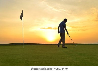 Young man playing golf at sunset