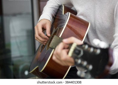 Young man playing guitar. Close up. Focus on the right hand. With shallow depth of field.