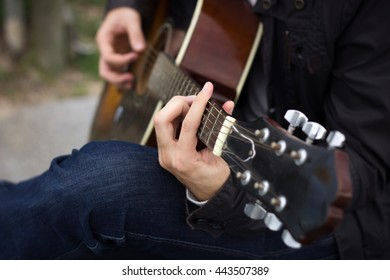 Young man playing guitar. Close up. Focus on the left hand. With shallow depth of field.