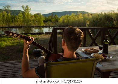 Young man playing guitar and drinking wine alone. Covid-19 quarantine.