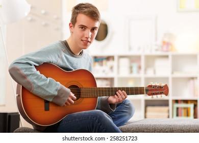 Young man playing guitar at his home