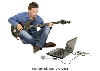 Young man playing guitar with a laptop