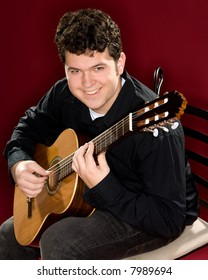 Young man playing a guitar and making direct eye contact with the viewer. Red background.