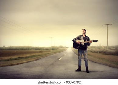 Young man playing the guitar on a countryside road