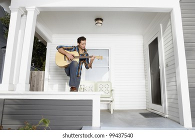 Young man playing guitar on porch
