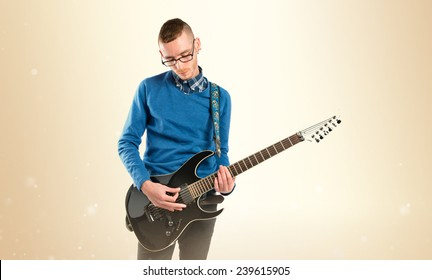 Young man playing guitar over ocher background