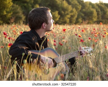 Young man playing guitar in poppy field on sunset