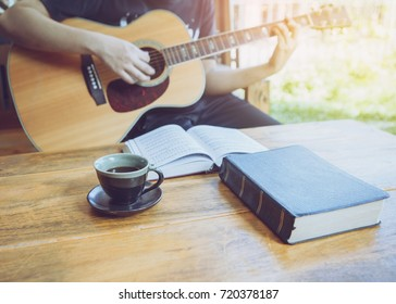 A young man is playing guitar and sing a song from Christian hymn  book with a cup of coffee and bible  on wooden table over garden background