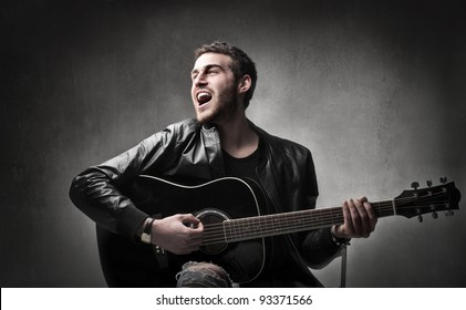 Young man playing the guitar and singing