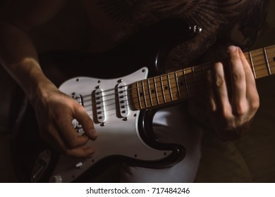 the young man is playing the guitar. man in tattoos playing guitar at home