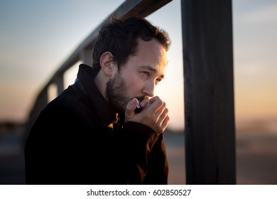 Young man playing the harmonica on the beach on sunset background. With shallow depth of field.