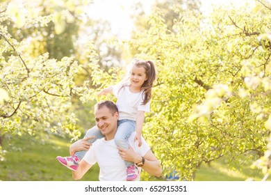 young man is playing with his daughter in the nature. The father is standing and carrying girl on his back. happy family having fun outdoors Happy family playing in nature