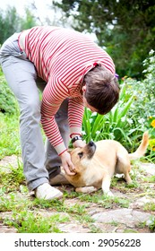 young man playing with his dog in the garden