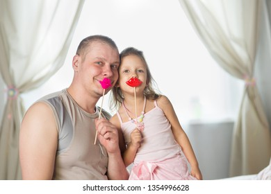 young man playing with his little daughter in the nursery