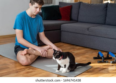 Young man is playing with his pet cat while doing fitness workout indoors in the living room.Stay home during COVID-19 quarantine  concept.