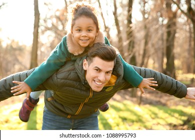 Young man playing with little African-American girl outdoors on sunny day. Child adoption