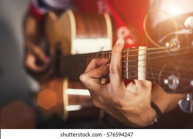 Young man playing on acoustic guitar.